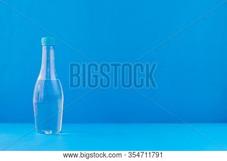 Bottle Of Water On Blue Background, View From Front Table.