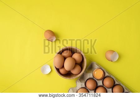 Fresh Eggs On Wooden Plate On Yellow Background.
