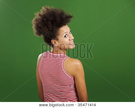 Happy African woman over a green background looking back
