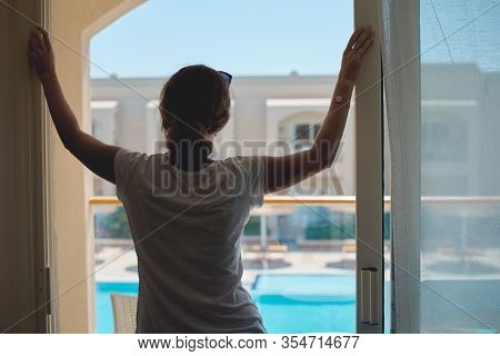 Woman Standing Near Window On The Hotel Balcony And Gazing On Swimming Pool