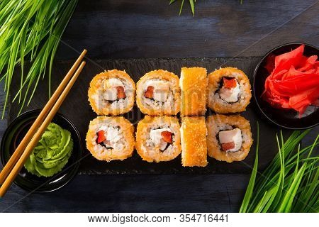 Set Of Fried Sushi Rolls With Wasabi And Ginger On A Black Background. Japanese Oriental Cuisine