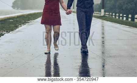 Man And Woman Hold Hands Together. Couple Is Walking Along The Road On The Promenade. Walk In Bad We