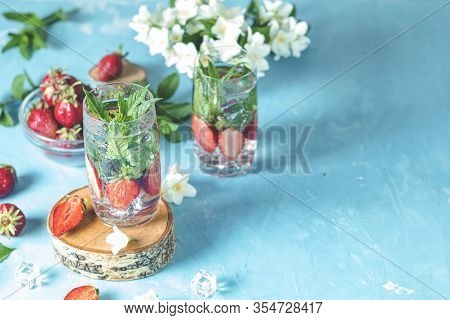 Detox Infused Water With Strawberry And Mint In Highball Glasses On Blue Concrete Table Background,