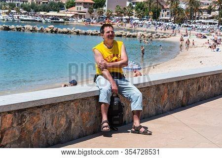 Port De Soller, Spain - June 02, 2016: Tourist On The Wall Of The Beach Promenade Of Port De Soller
