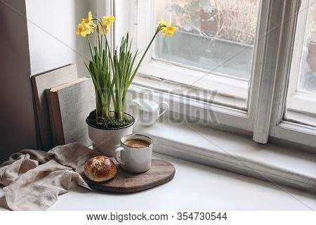 Cozy Easter Spring Still Life Scene. Cup Of Coffee, Sweet Bun, Books, Wooden Cutting Board, Milk Pit