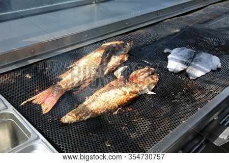 Cooked Fish. Fish being barbecued on a grill outside. BBQ Food. Fresh Fish being cooked outdoors on a grill at a Restaurant. Fish is a healthy food eaten by Humans and Animals world wide. Grilled meat