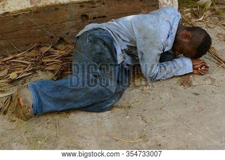 Young Homeless African Man Lying Down In The Streets