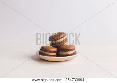 Tasty French Macarons On A Plate. White Background. Chocolate Macarons With Peanuts. Place For Text.