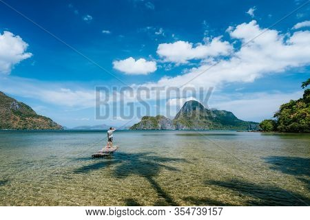 Man On Bamboo Float In Shallow Lagoon With Panoramic View Of Shallow Lagoon And Islands In Cadlao Ba