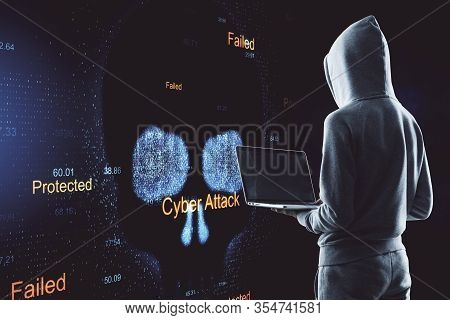 Hacker Holding Laptop With Cyber Skull And Hacker Attack Interface. Virus Attack And Malware Concept