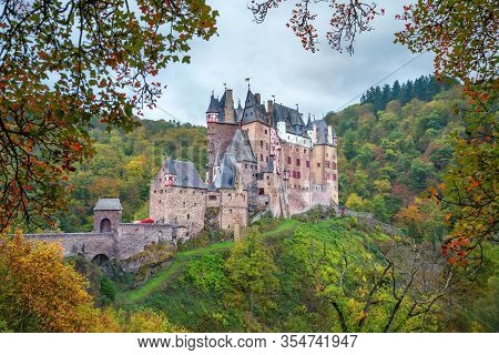 Eltz Castle In Autumn - Famous Hilltop Castle Nested In The Forest Hills Above The Moselle River Bet