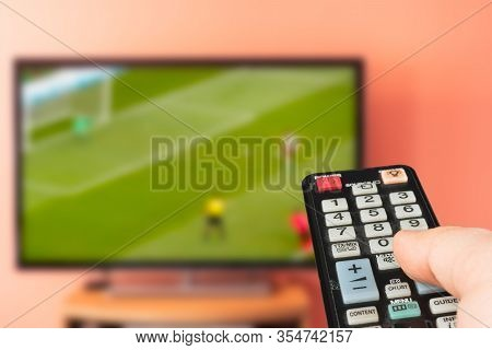 Caucasian Man Watching Soccer Or Football On Tv At Home. Changing Channels And Adjusting Volume With