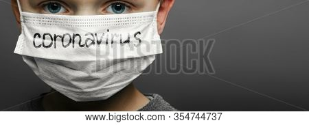 Face of a mask-wearing boy with fear in the eye Close-up on a gray background.