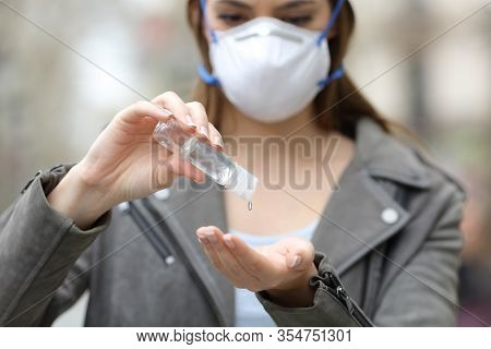 Close Up Front View Of A Woman With Protective Mask Using Hand Sanitizer Preventing Contagion On Str