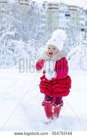 Enjoyment In The Winter Season. A Beautiful Little Girl In A Red Coat And White Hat With A Scarf Run
