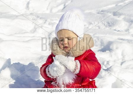 Winter Activities For Children. A Little Girl Is Trying To Make A Snowball. She Is Dressed In A Brig
