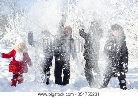 A Group Of Children Throw Snow And Enjoy The Winter Games In The Fresh Frosty Air. Snow-covered Tree