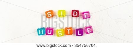 Side Hustle Phrase Made Of Cube Beads Of Different Colors On White Concrete Background. Conxep Of Ad