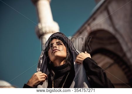 Portrait of a gorgeous arabic girl covering her head with a stylish scarf, Islamic fashion, luxury beauty, authentic arab beauty