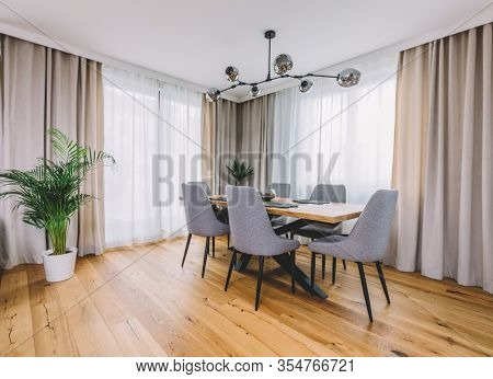 Dining room with wooden table and floor in modern apartment. Interior design