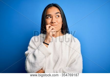 Young beautiful asian sportswoman wearing sweatshirt standing over isolated blue background with hand on chin thinking about question, pensive expression. Smiling with thoughtful face. Doubt concept.