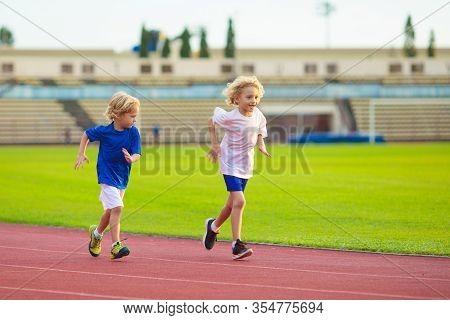 Child Running In Stadium. Kids Run On Outdoor Track. Healthy Sport Activity For Children. Little Gir