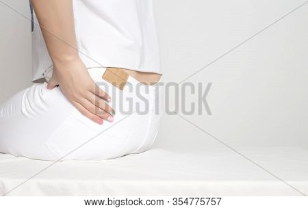 A Girl In White Clothes Holds By The Hip In Which Pain And Inflammation. Femur Osteoarthritis Concep