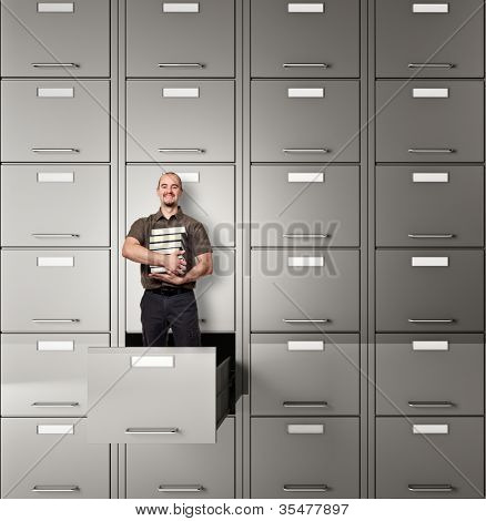 man with book in file cabinet drawer