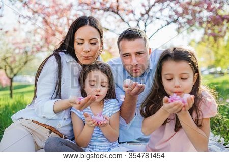 Young Parents With Small Daugthers Sitting Outside In Spring Nature.