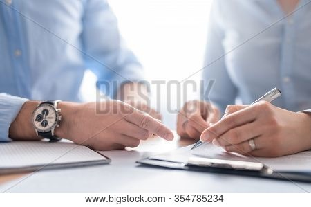 Business People Negotiating A Contract. Human Hands Working With Documents At Desk And Signing Contr