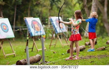 Archery For Child. Little Girl With Bow And Arrow. Kids Shoot On Tropical Island. Target On Outdoor