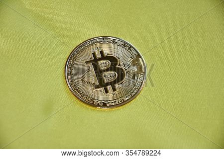 Shiny Physical Bitcoinin Yellow Background - Blockchain Technology.