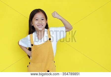 Happy Asian Little Child Girl Showing His Muscle With Looking Camera Isolated On Yellow Background W
