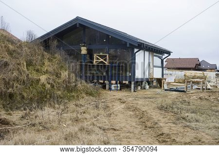 A Worker Standing On The Trestles And Painting A House, Outdoor Shot