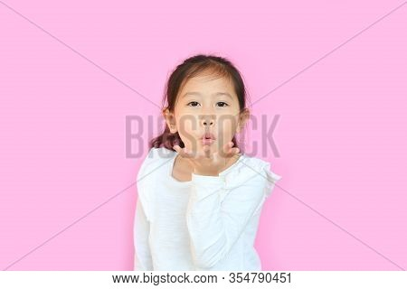 Asian Little Child Girl Blowing A Kiss With Hand On Air Being Lovely Isolated On Pink Background. Ki