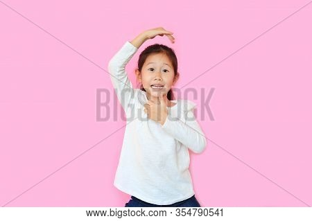 Cheeky Little Asian Kid Girl With Expression Monkey Face And Hands Isolated On Pink Background. Amus