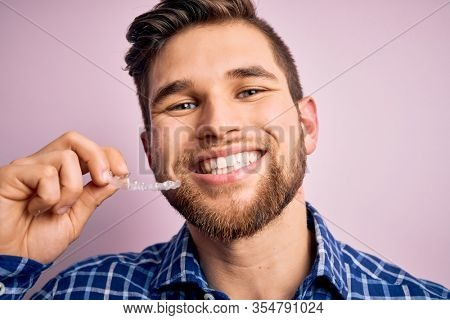 Young blond man with beard and blue eyes holding dental aligner over pink background with a happy face standing and smiling with a confident smile showing teeth