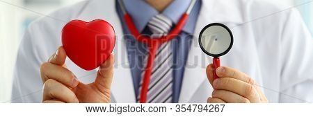 Male Medicine Doctor Holding Red Heart And Stethoscope Head In Front Of Chest Closeup. Medical Help