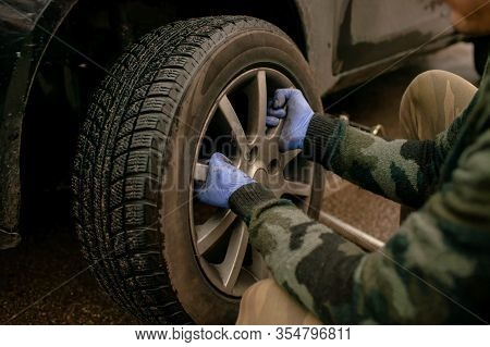 Man Unscrews Bolts Of The Rear Wheel The Car To Change The Tires