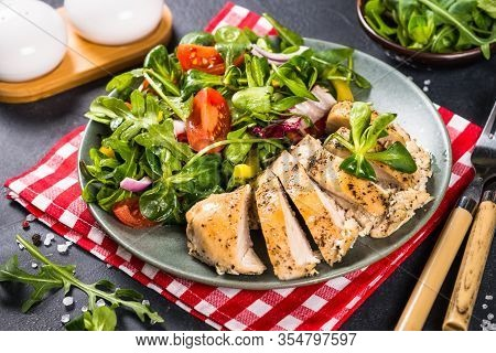Baked Chicken Breast With Green Salad On Black Background. Healthy Food, Keto Diet, Paleo Diet.