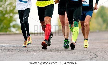 Legs Male Runners In Compression Socks And Kinesio Tape Run Marathon