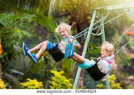 Child Playing On Outdoor Playground. Kids Play On School Or Kindergarten Yard. Active Kid On Colorfu