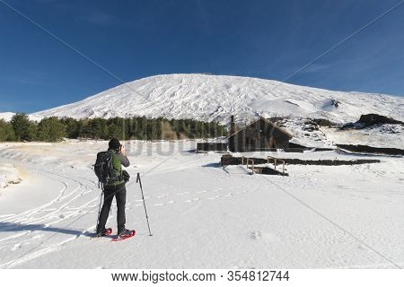 snow covered Galvarina stone refuge below Etna Mount, hiker with snowshoes take a picture, Sicily