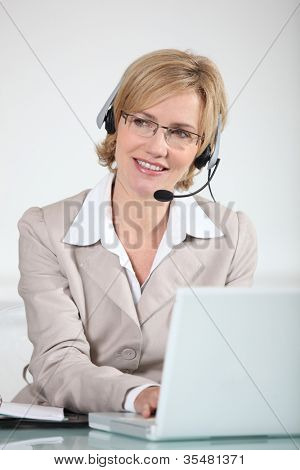 Woman using a telephone headset at a laptop computer