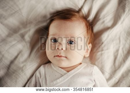 Closeup Portrait Of Cute Caucasian Newborn Baby. Adorable Funny Child Infant With Blue Grey Eyes And