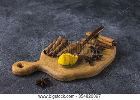 Set Of Ingredients For The Preparation Of A Traditional Indian Drink - Golden Milk On A Dark Backgro
