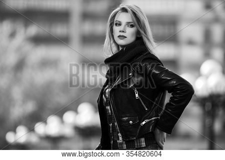 Young fashion blonde woman walking on city street  Stylish female model in black leather jacket and snood scarf