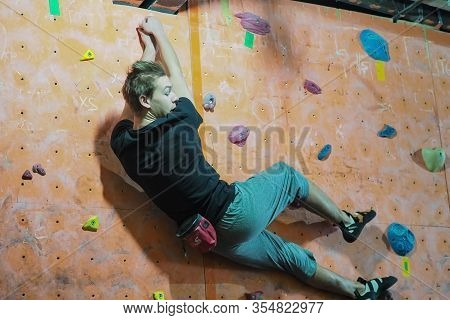Climber In A Boulder Gym. Man Climbing Bouldering Problem. Colorful Volumes And Holds On A White Wal
