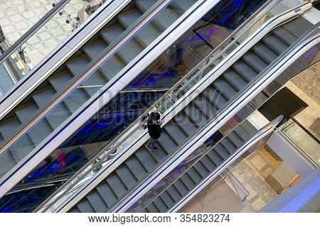 One Customer On Escalator Stairs Inside A Giant Modern Shopping Center. The Concept Of Unprofitabili