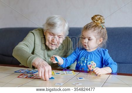 Beautiful Toddler Girl And Grand Grandmother Playing Together Pictures Lotto Table Cards Game At Hom